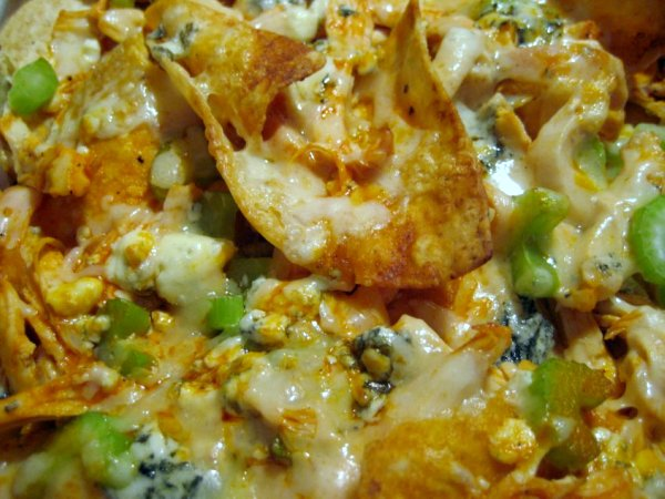a closeup of Buffalo chicken nachos with melted cheese and scallions