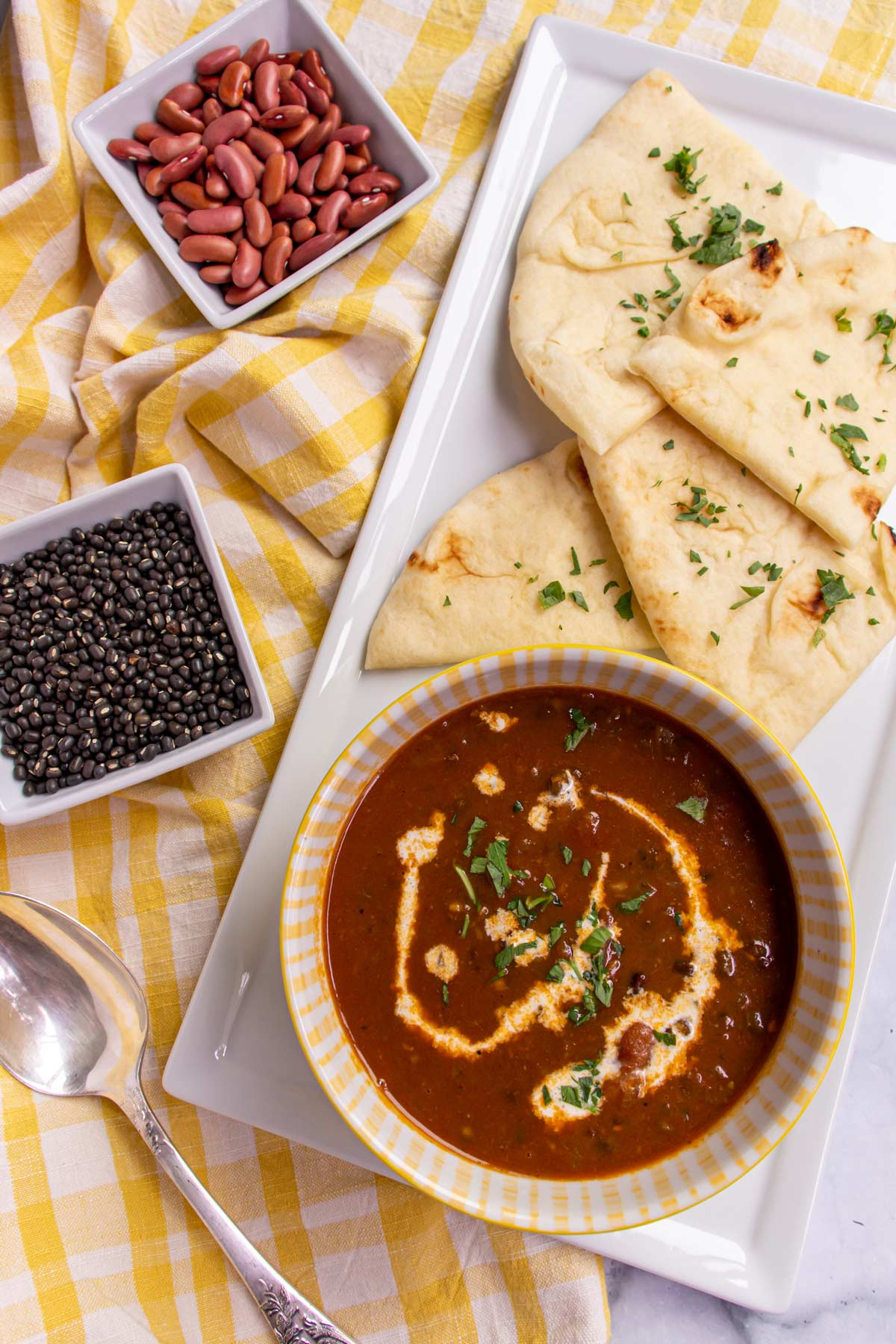 A bowl of brown curry, naan bread, bowls of dry lentils and beans, and a spoon.