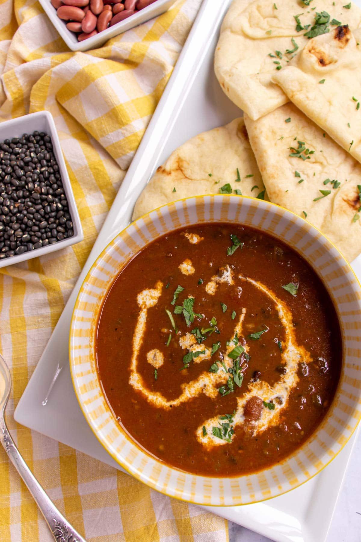 A bowl of dark brown stewed lentils with naan bread and a yellow gingham towel.