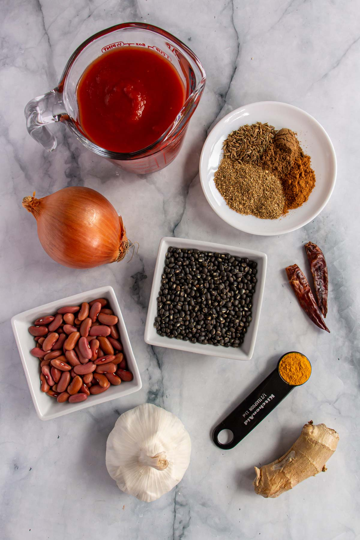 Ingredients for dal makhani on a white marble background.
