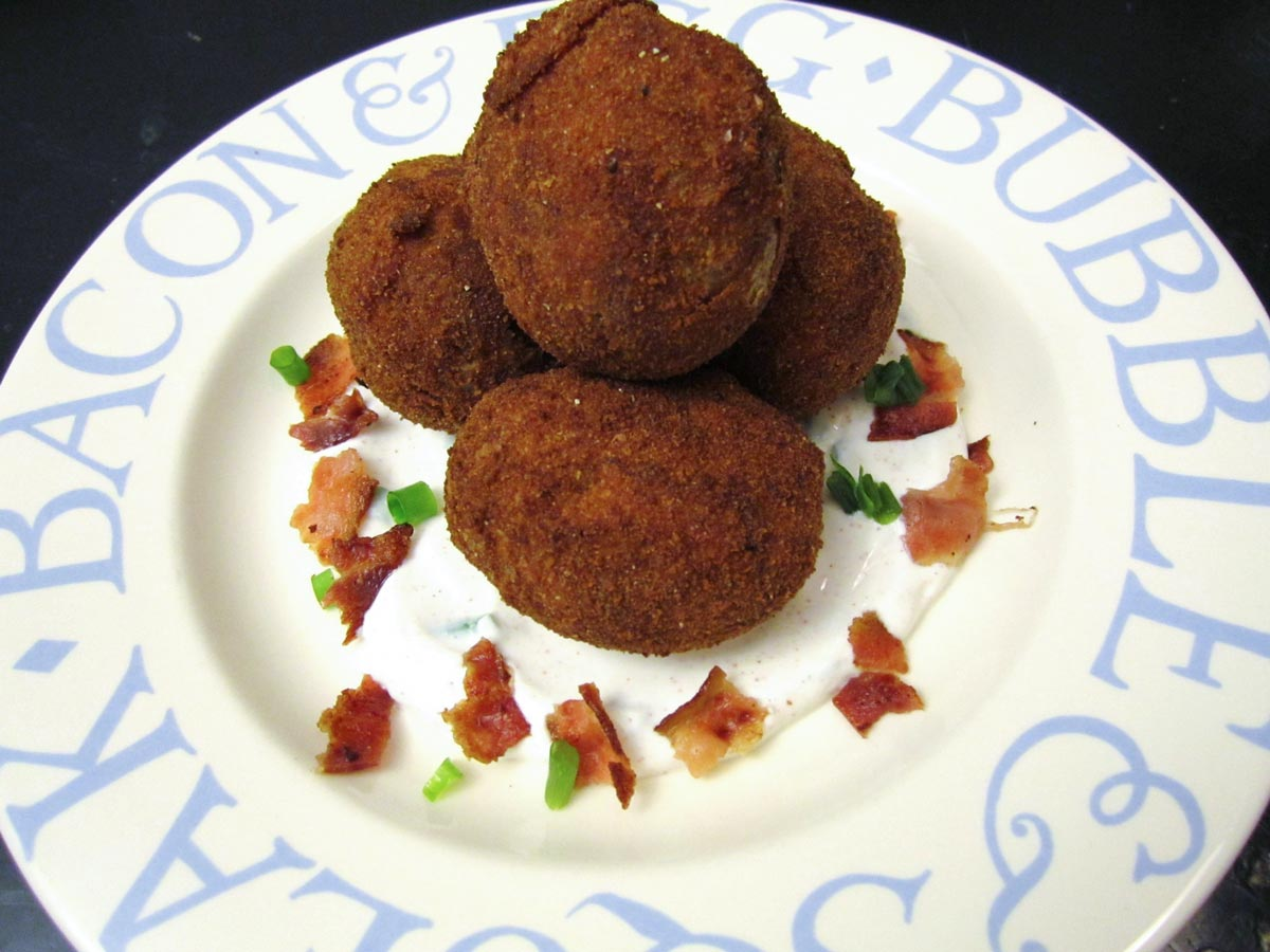 A pile of breaded fried small potatoes with bacon and scallions around it.