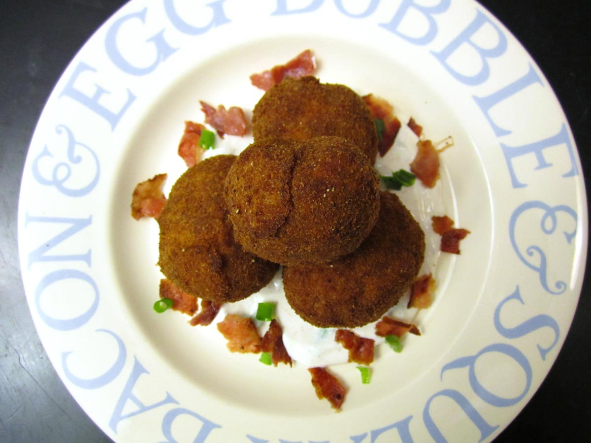 A pile of breaded fried potatoes with bacon and scallions.