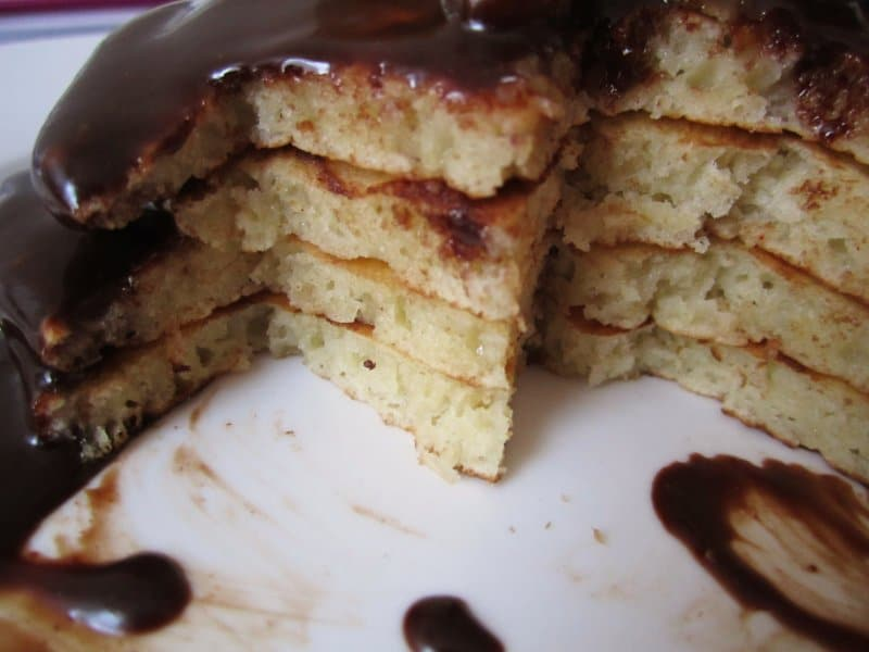 closeup of a half-eaten plate of pancakes with chocolate sauce on a white plate