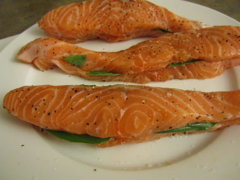 raw fillets of salmon sandwiched around basil leaves on a white plate