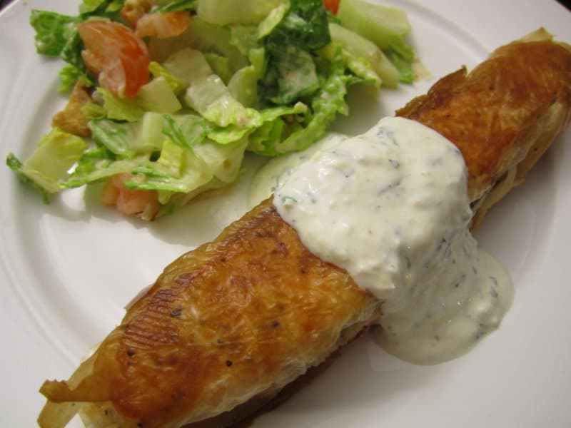 closeup of a phyllo wrapped salmon with white sauce on top and salad on the side