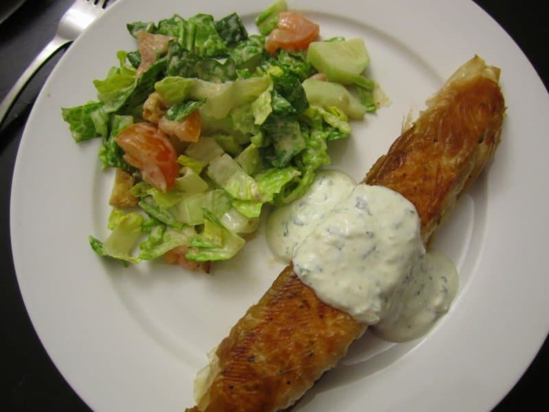 overhead view a plate of a crispy salmon fillet topped with creamy sauce next to salad