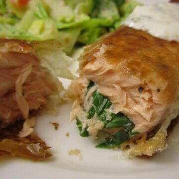 A closeup of cooked salmon stuffed with basil on a white plate