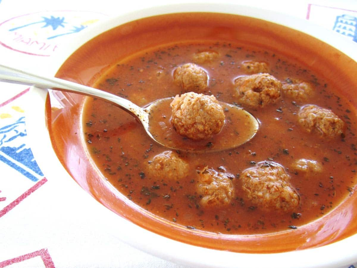 A spoon is lifting a meatball out of the bowl of Armenian meatball soup.
