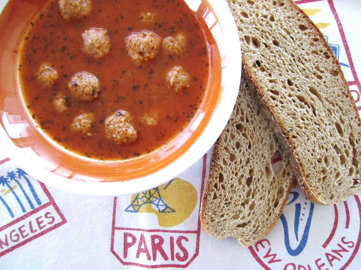 Closeup of a bowl of Armenian meatball soup with wheat toast next to the bowl.