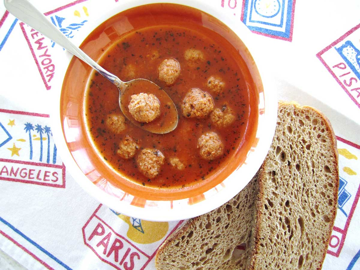 A bowl of Armenian meatball soup with sliced wheat toast next to the bowl.