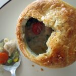 overhead view of a half-eaten pot pie with a spoonful of chicken, carrots, and peas