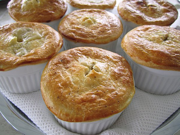 individual pot pies in white ramekins topped with rounds of pie crust