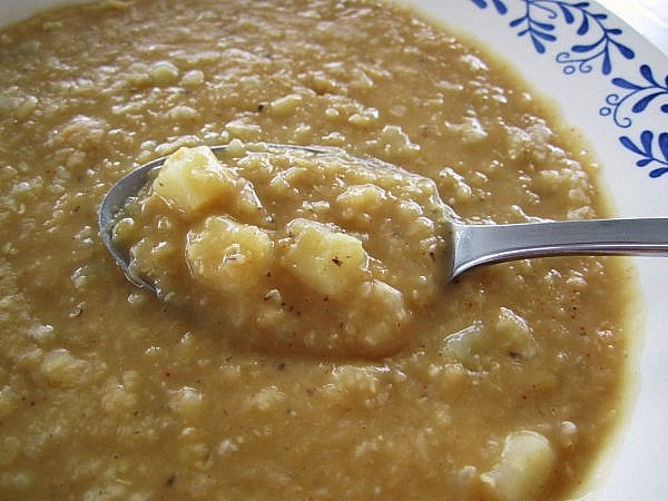 a closeup of a spoonful of red lentil soup with cubes of potato and rice