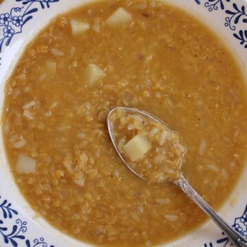 A bowl of red lentil potato soup with rice with a spoon lifting some out.