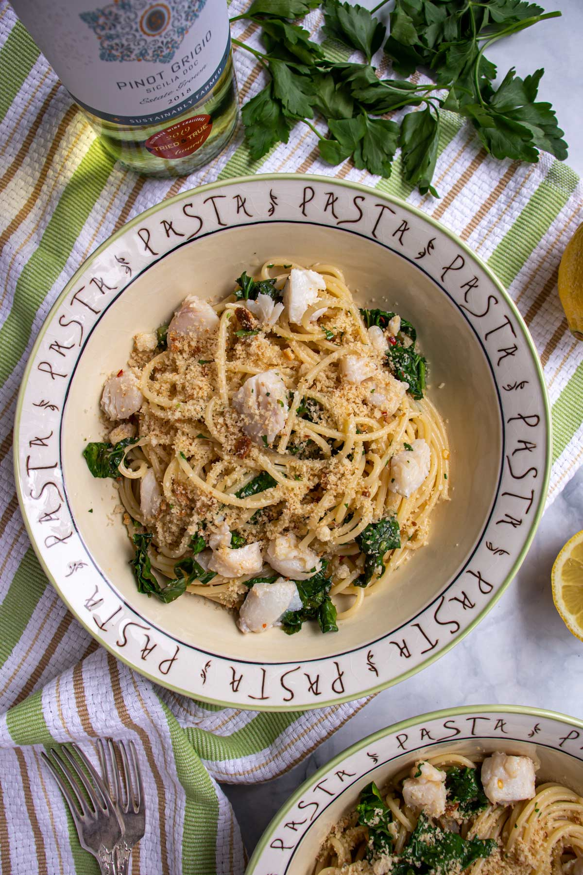 A bowl of spaghetti with broccoli rabe, small pieces of cod, and breadcrumbs on top.