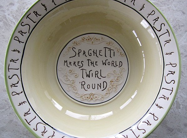 overhead view of a bowl that says Spaghetti Makes the World Twirl \'Round on the bottom