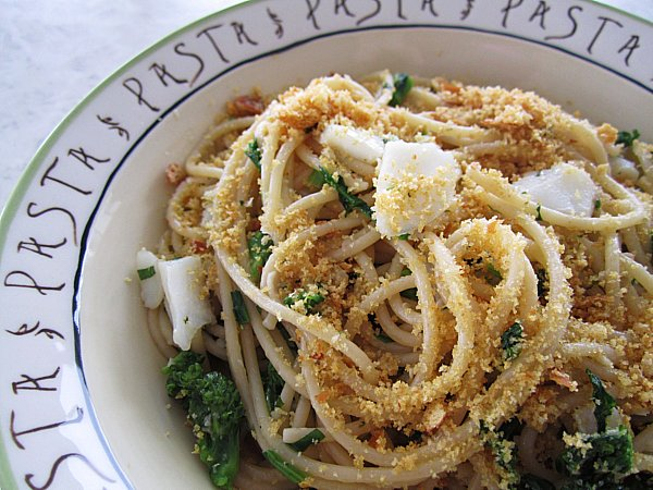 closeup of a bowl of spaghetti with flaked cod, broccoli rabe, and breadcrumbs on top
