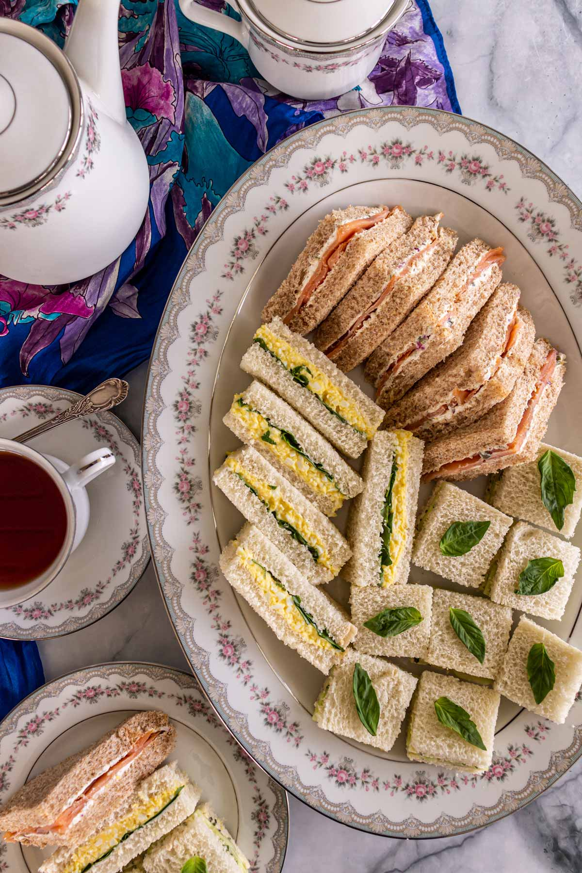 An oval platter of assorted tea sandwiches, a tea pot, and a cup of black tea.