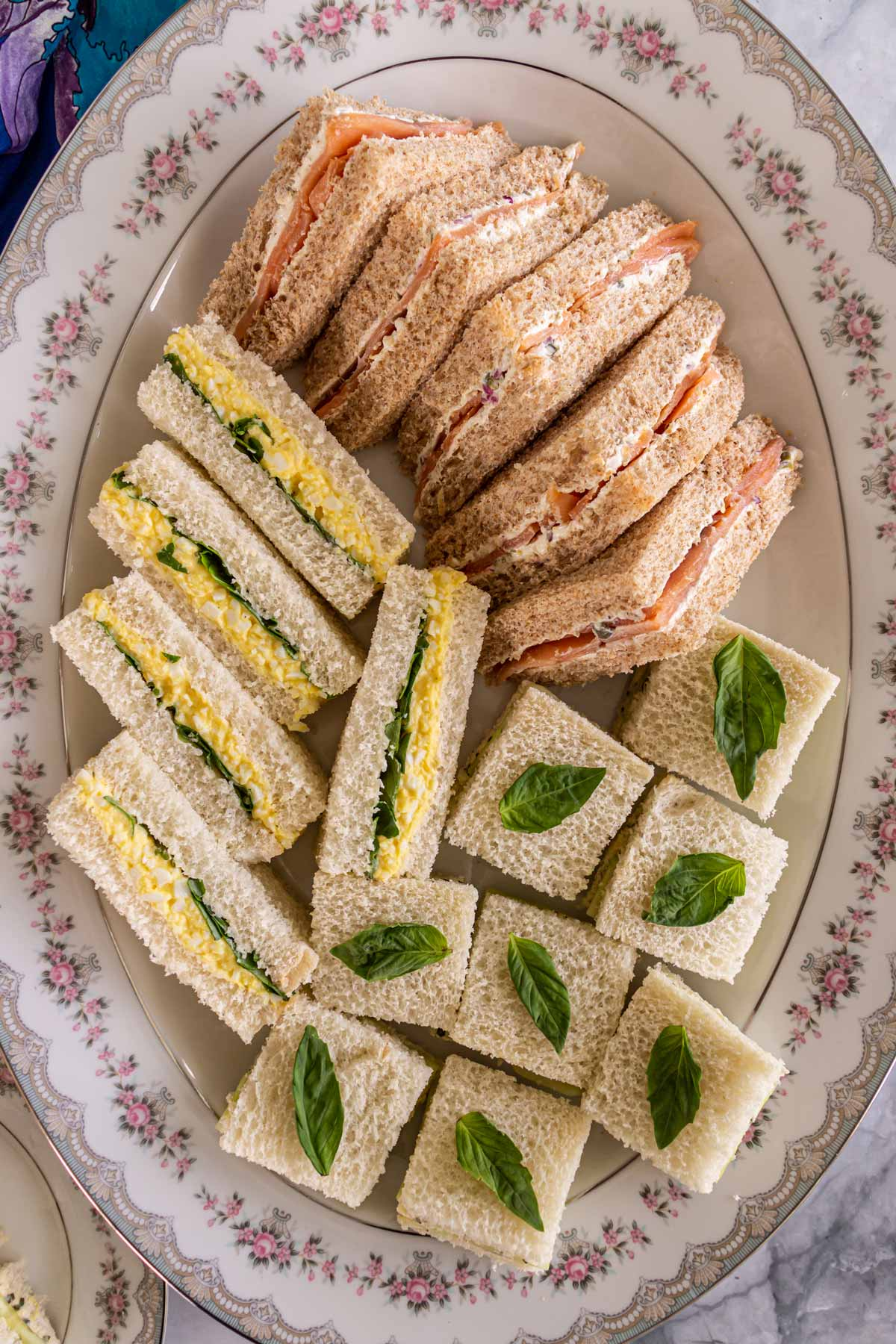 An oval platter covered with an assortment of English tea sandwiches.