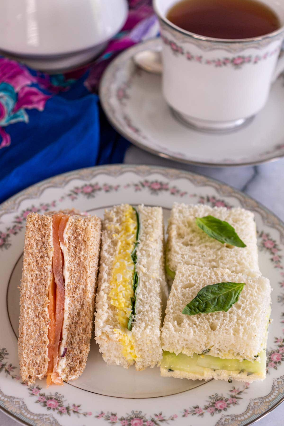 An assortment of tea sandwiches on a china plate in front of a cup of tea.