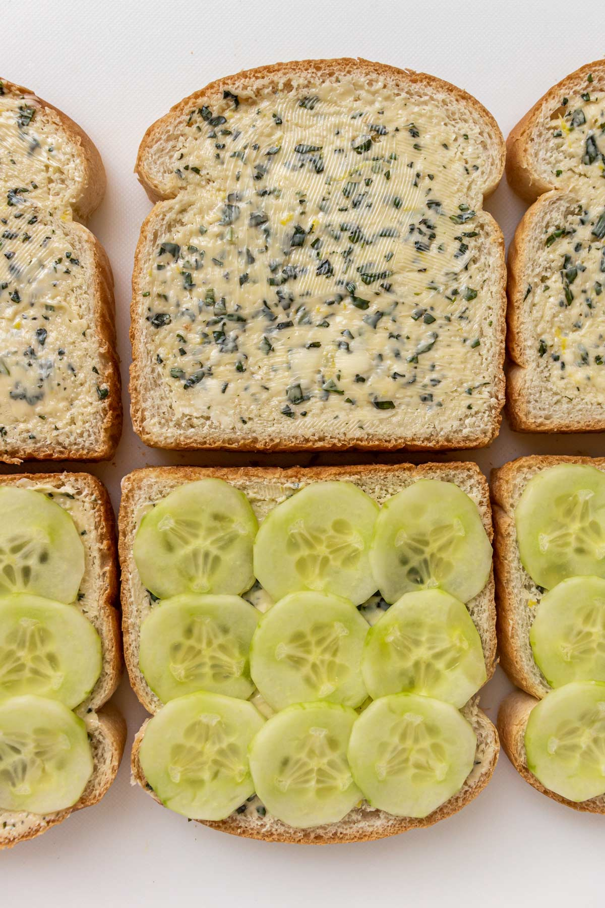 Sandwich bread spread with lemon herb butter with sliced cucumber slices on the other halves.