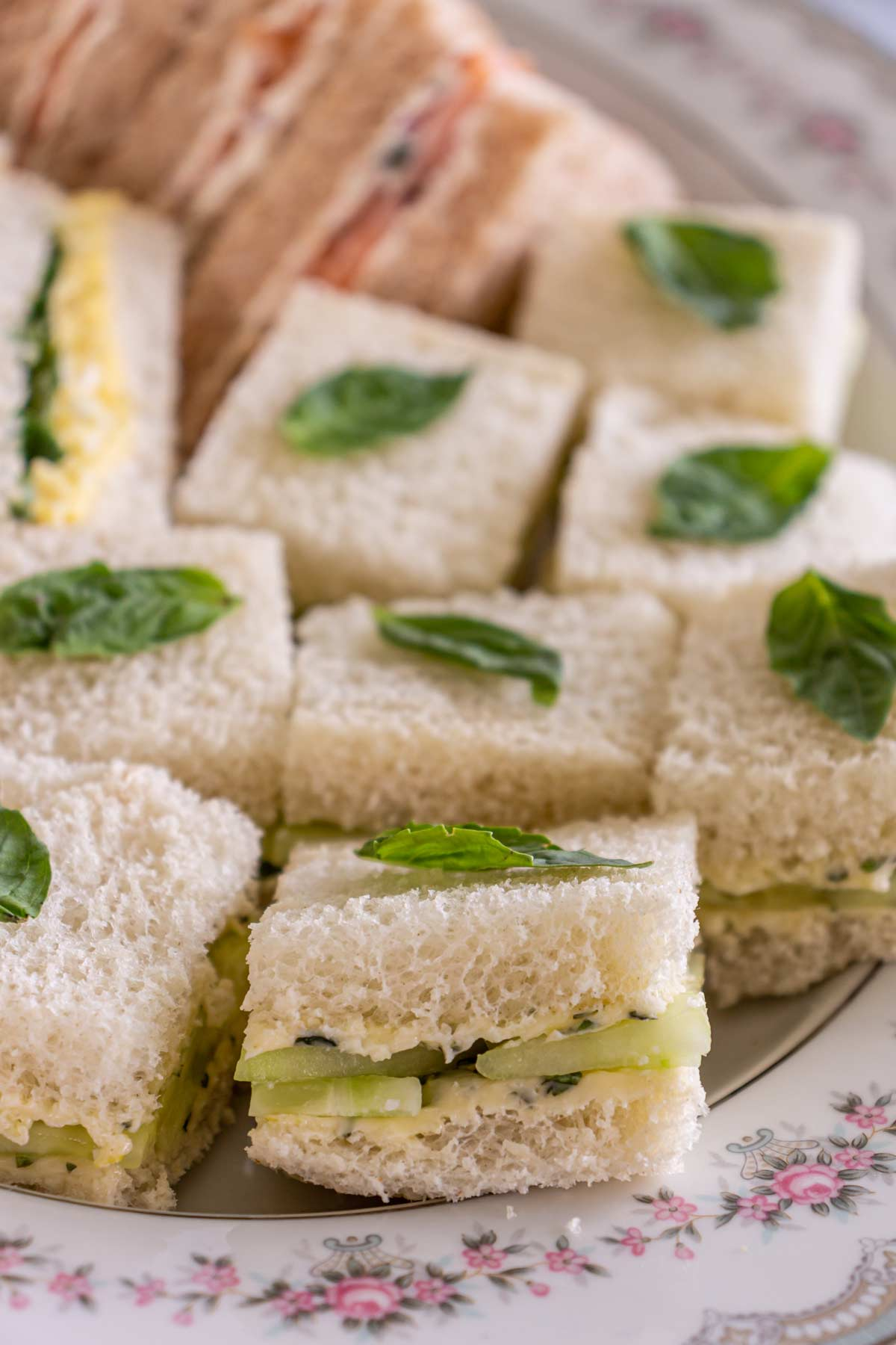 Closeup of small square English cucumber sandwiches topped with fresh basil leaves on a platter.