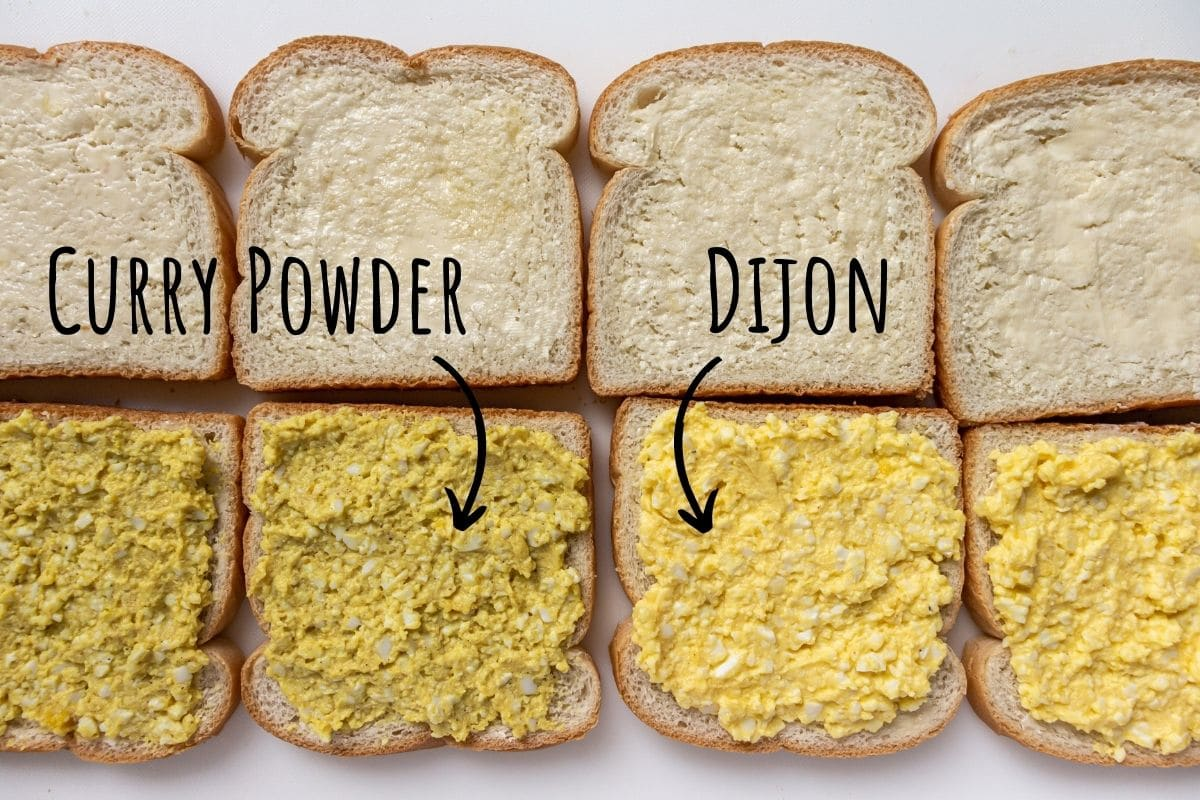 Two varieties of egg salad with curry powder and Dijon mustard spread on slices of bread.