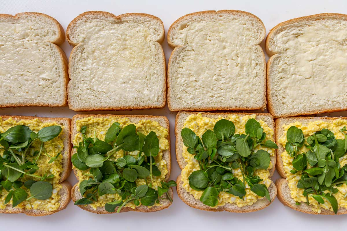 Assembling egg and cress sandwiches on a white surface.