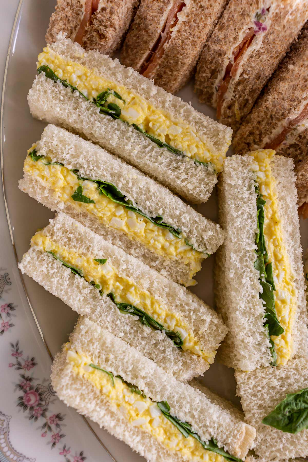 A closeup of egg and cress finger sandwiches on a china platter.