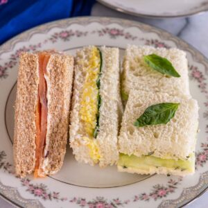 Closeup of an assortment of tea sandwiches on a floral china plate.