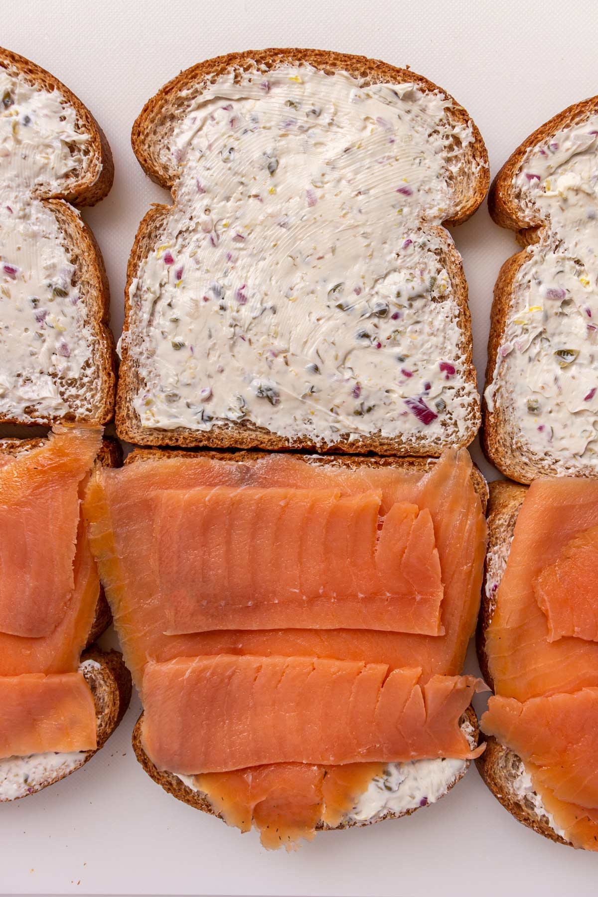 Assembling a smoked salmon sandwich with cream cheese on a white surface.