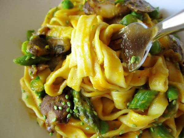 a closeup of yellow fettuccine with mushrooms and asparagus twirled around a fork