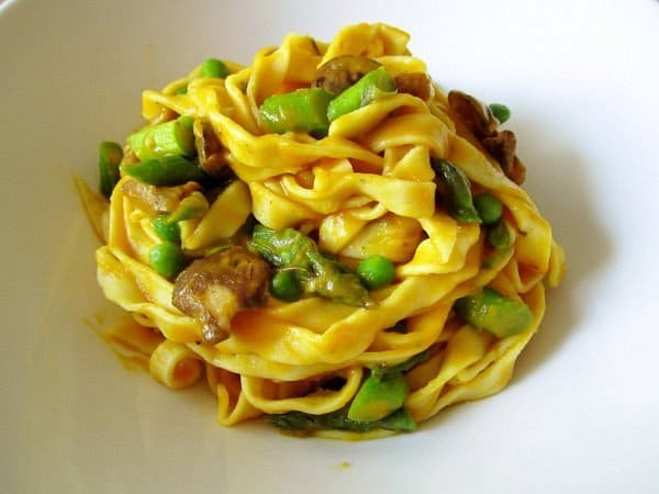 fresh curry fettuccine with pureed carrot sauce, asparagus, peas, and wild mushrooms
