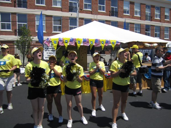 a group of cheerleaders in yellow tee shirts and black shorts with black pompoms