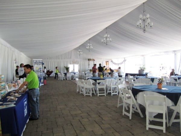 a large white tent with tables and white chairs and some people milling around