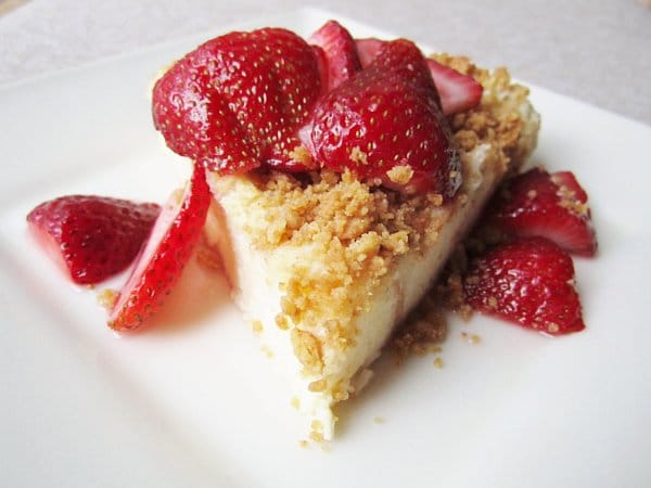 a wedge of bread pudding that resembles cake topped with crumbs and strawberry slices