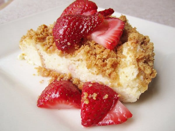 a wedge of crumb topped bread pudding with sliced strawberries over the top and sides
