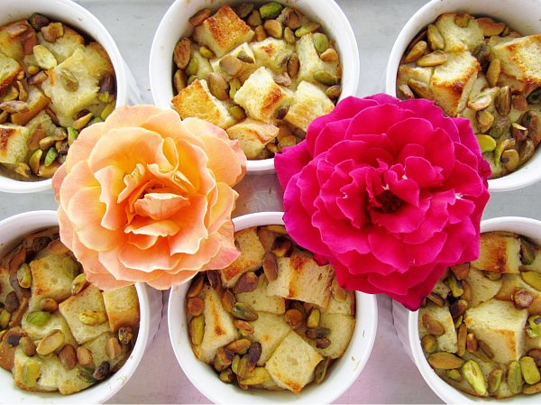 overhead view of six ramekins of bread pudding with two roses in between