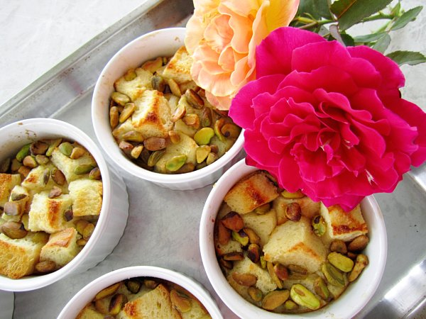 white ramekins of bread pudding on a baking sheet with two roses to the side