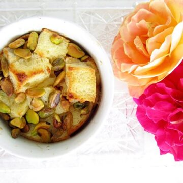overhead closeup of bread pudding with pistachios in a ramekin next to colorful roses