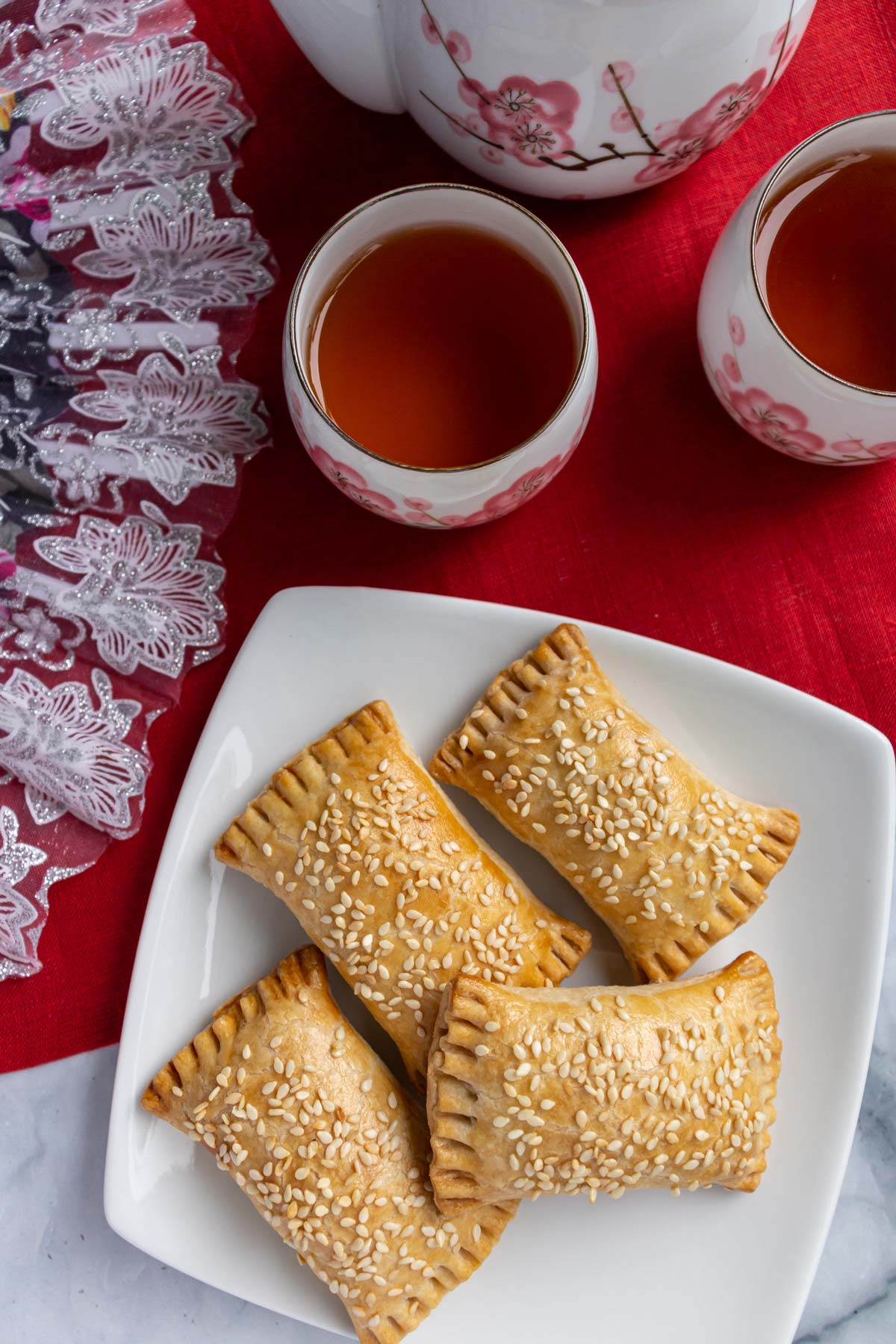 Four sesame seed topped Chinese pastries on a square white plate next to small tea cups.