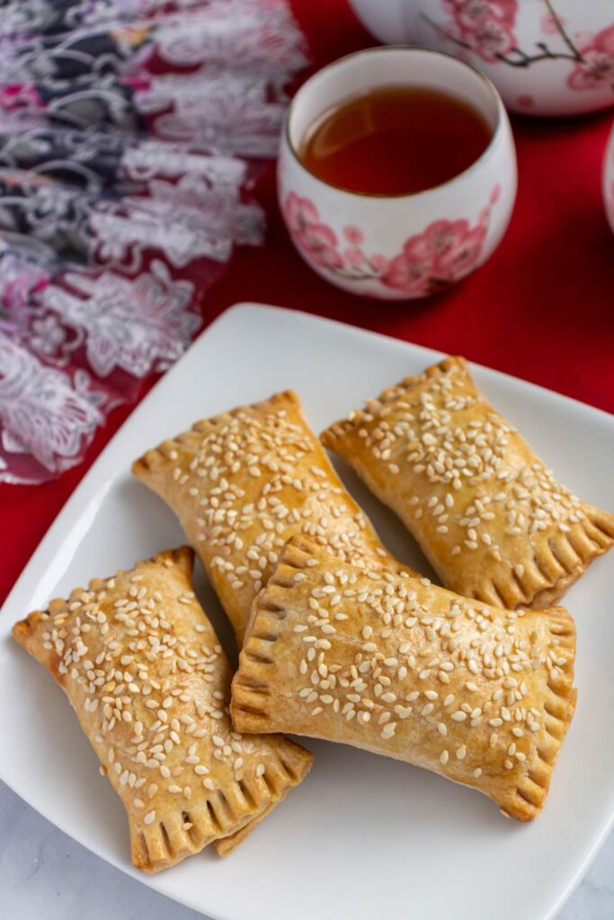 Sesame seed topped rectangular pastries on a square white plate with tea cups in the background.