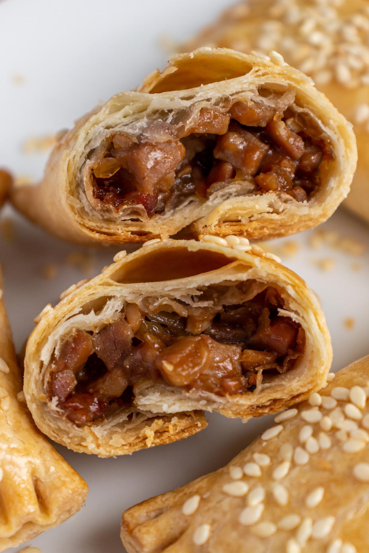 Closeup of a flaky Chinese pastry broken in half to show the char siu pork filling.