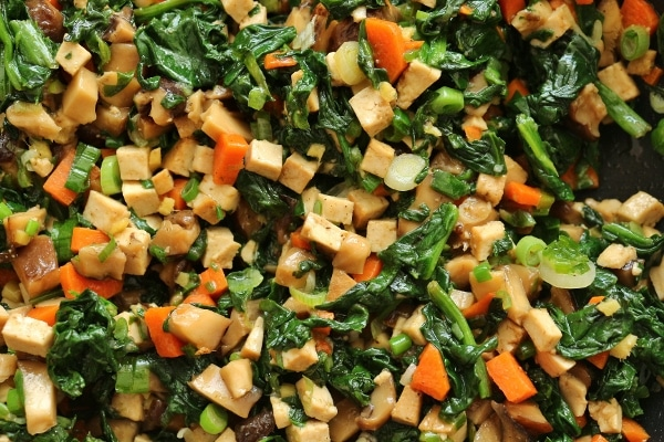 a combination of chopped tofu, mushrooms, carrots, spinach, and scallions
