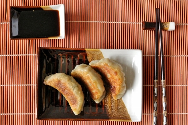 overhead view of a small rectangular plate of dumplings with chopsticks and dipping sauce beside it