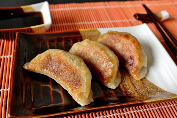 closeup of three pan-fried vegetable dumplings on a brown and white rectangular plate
