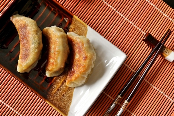 overhead closeup of three pan-fried dumplings on a white and brown plate with chopsticks