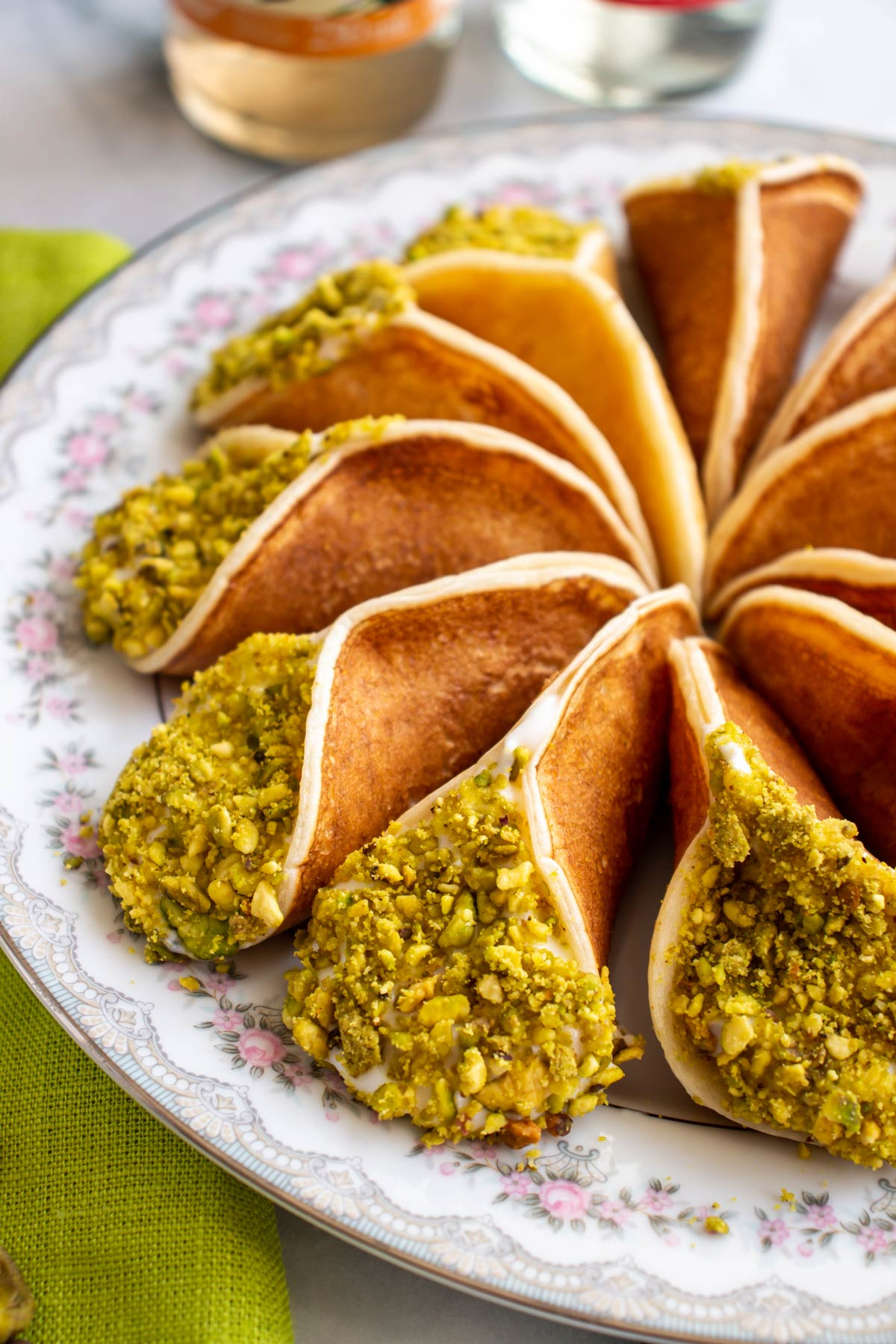Closeup of atayef pancakes with crushed pistachios fanned out on a floral china plate.