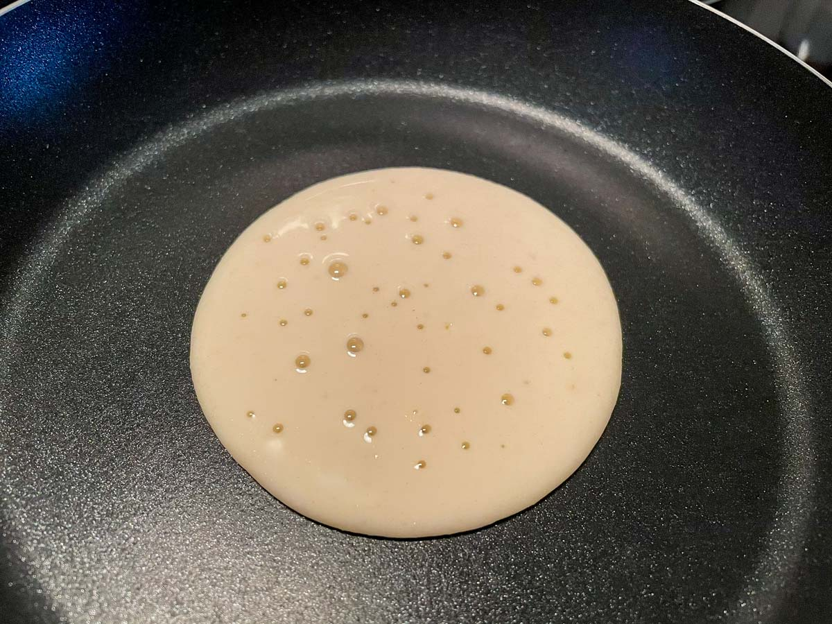 A small pancake with bubbles on the surface cooking in a nonstick skillet.