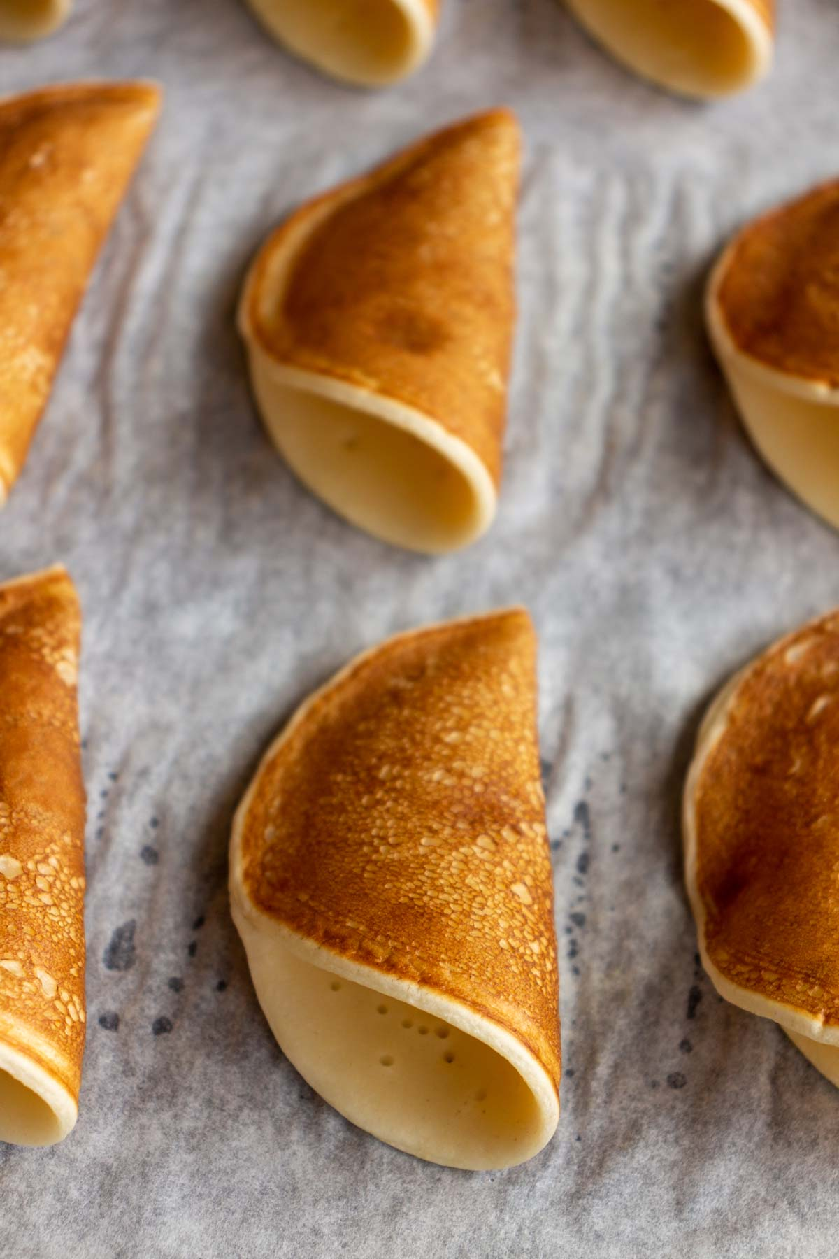 Cone shaped qatayef pancakes resting on their sides on parchment paper.